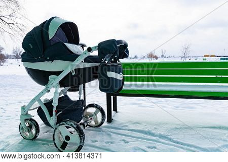 The Child Sleeps In A Stroller. A Baby Stroller Stands In The Park By The Bench In Winter.