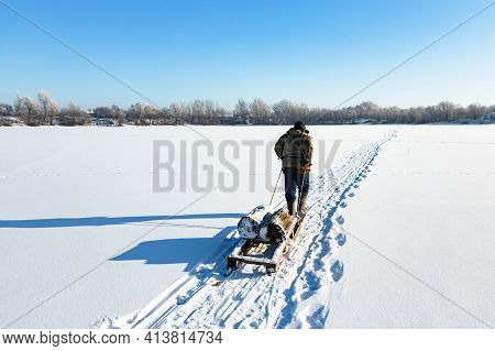 A Lonely Old Hermit, In Winter, Crosses The River On Ice And Pulls A Sled With Firewood For Heating