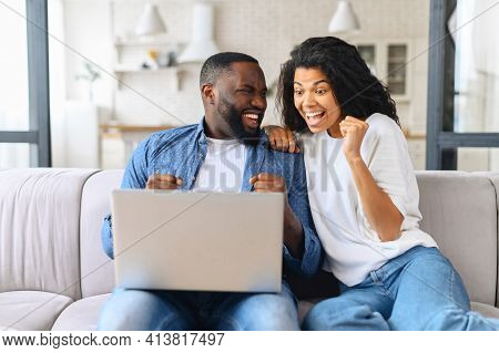 Overjoyed Cheerful Multiracial Couple Celebrating Good News Looking At The Laptop Screen, Young Exci
