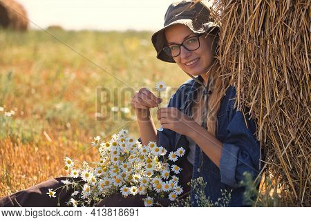Girl In A Hat With A Bouquet Of White Daisies