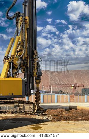 Hydraulic Drilling Rig Against The Blue Cloudy Sky. Vertical Image. Installation Of Bored Piles By D