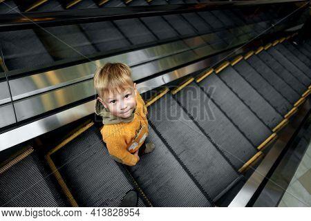 A Little Boy Himself Rides An Escalator 2021