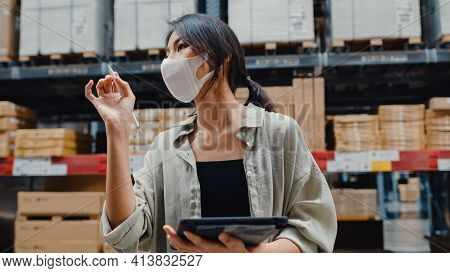 Young Asia Businesswoman Manager Wear Face Mask Looking For Goods Using Digital Tablet Checking Inve