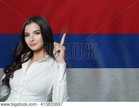 Woman Pointing Up On Serbian Flag Background. Education Or Business Concept