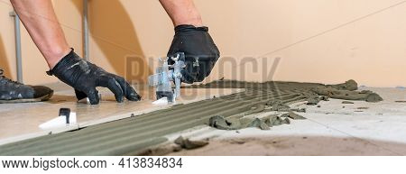 Workers Are Using Plastic Clamps And Wedges To Leveling The Ceramic Tile On The Floor. Tile Leveling