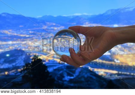 A Glass Lens Ball And Overview Of Trento City In Night Time