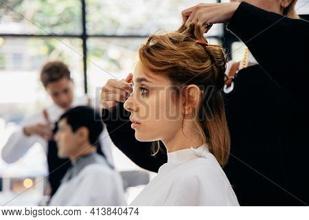 Beautiful Young Caucasian Woman Sitting In Modern Parlour With Wrap Around Getting A Haircut With Ha
