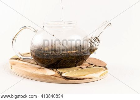 Boiling Water Is Poured Into A Glass Teapot With Aromatic Herbal Tea Standing On A Wooden Juniper St