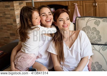 Portrait Of Two Sisters And A Little Girl Sitting On The Couch, Smiling. Concept: Family, Sisters, H