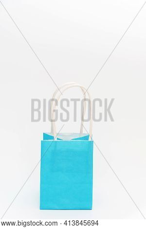 Close-up Of Little Cute Blue Package On White Background. Empty Craft Pack With Handle For Present.