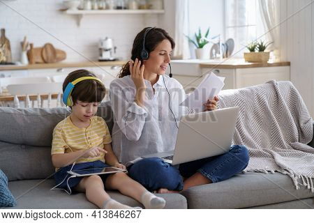 Freelancer Mother Sitting On Couch At Home Office During Lockdown, Remote Work On Laptop. Child Usin