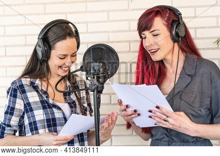 Happy Young Women With Scripts Smiling And Resting Near Microphone During Break In Film Dubbing Sess