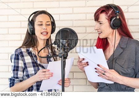 Happy Young Voice Actresses In Headphones Smiling And Reading Script Near Microphone While Creating