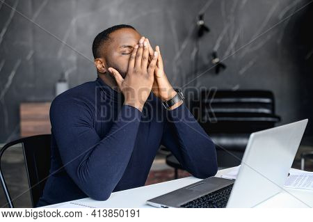 Exhausted African-american Male Employee Covered Face With A Palms, Tired Black Businessman Sits At