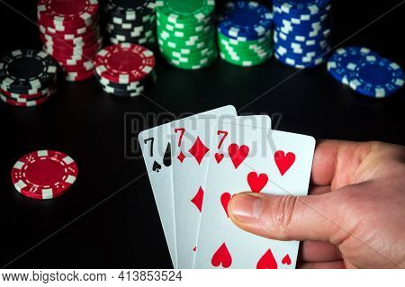 Poker Cards With Three Of A Kind Or Set  Combination. Close Up Of A Gambler Hand Is Holding Playing