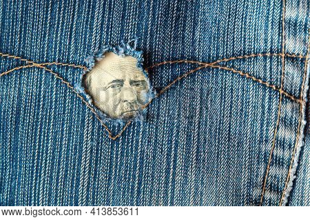Hole In The Pocket Of Denim Pants From Which Dollars Are Visible. Symbolizes A Crisis Or A Hole In T