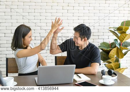 Young Asian Couple Wear Casual Clothing Relaxing While Sitting At Big Wooden Table In Modern Kitchen