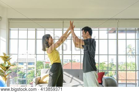 Young Asian Couple Wear Casual Clothing Giving High Five To Each Other And Smiling In Liveing Room