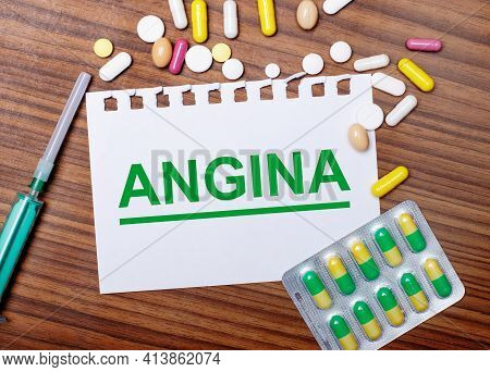 On A Wooden Table, A Syringe, Pills And A Sheet Of Paper With The Inscription Angina. Medical Concep