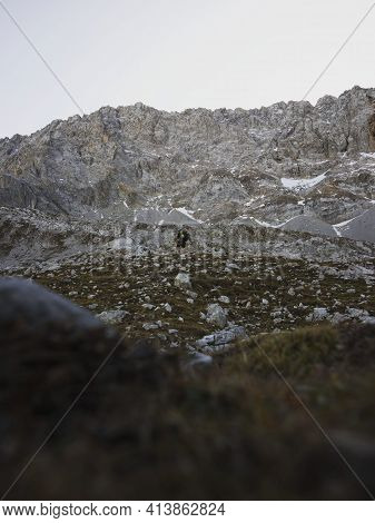 Autumn Fall Panorama Of Young Male Hiker Walking In Alpine Mountain Landscape At Lake Seebensee In E