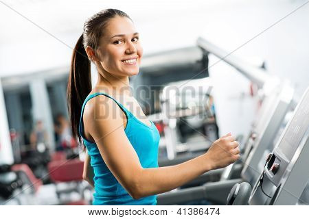 attractive young woman runs on a treadmill