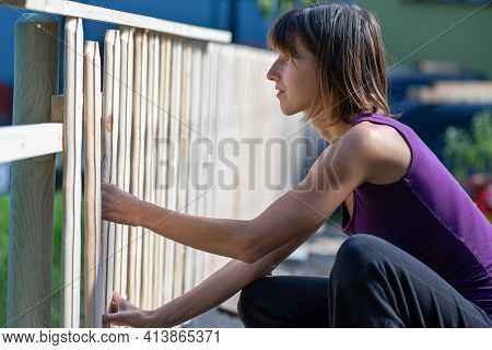 Young Woman In A Home Diy Project Making A Fence Of Wooden Planks Outside In Backyard.
