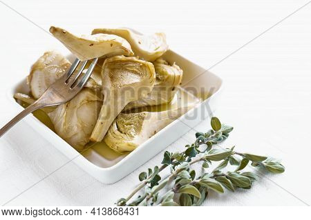 Artichokes Hearts Marinated With Olive Oil And Herbs. Pickled Artichoke With Garlic In White Plate O