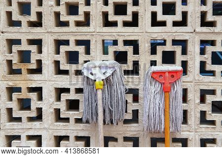 Funny Mops Heads Against Vent Wall. Used Wet Floor Mops Drying On Sun By Lean On Garage Or Warehouse