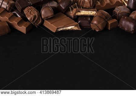 Variety Of Sweet Chocolate Pralines On Black Background. Top View With Copy Space.