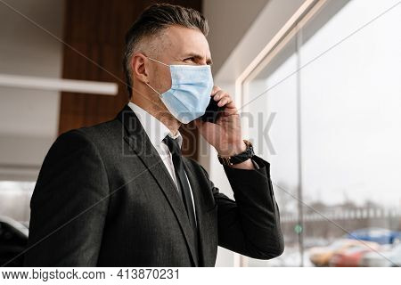 White businessman in face mask talking on cellphone at office