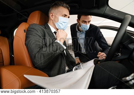 Mid white manager in face mask showing car to customer in showroom
