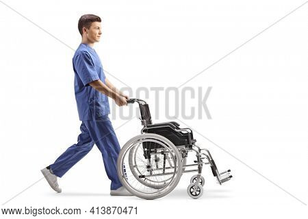 Full length profile shot of a male nurse pushing an empty wheelchair isolated on white background