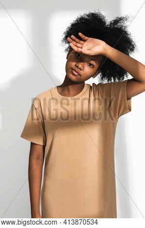 African American woman in brown t-shirt dress for apparel shoot