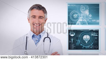 Portrait of caucasian male doctor smiling against screens of medical data processing. medical research and technology concept
