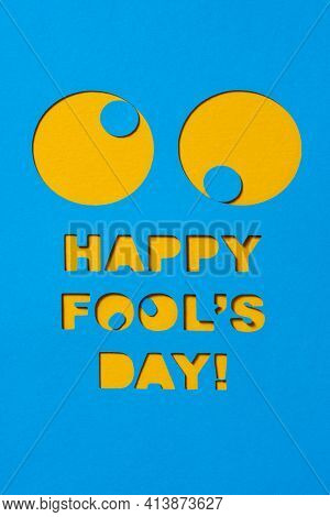 a pair of funny eyes and the text happy fools day cut out in a blue paperboard, against an orange background