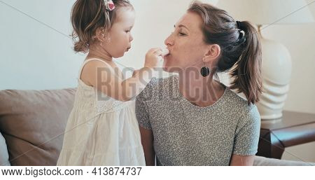 Toddler girl learns how to make up on her mother