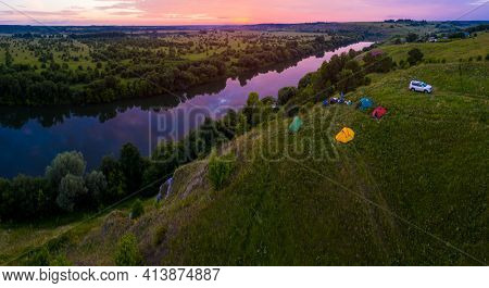 Group of tourists camping on the coast of the river of Sylva in Perm Kray in Russia during colorful pink sunset