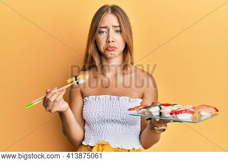 Beautiful young blonde woman eating omelette sushi using chopsticks depressed and worry for distress, crying angry and afraid. sad expression.