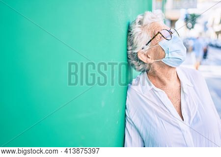 Elder senior woman with grey hair wearing coronavirus safety mask outdoors