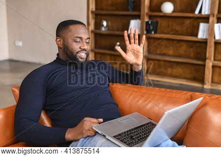 Video Call Concept. An African-american Freelancer Man Waving Hello Into Laptop Webcam, A Black Guy