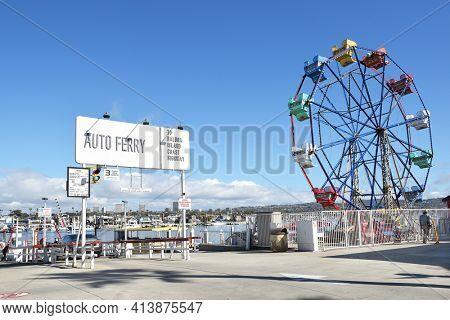 NEWPORT BEACH, CALIFORNIA - JANUARY 6, 2017: The Balboa Island Ferry and Ferris Wheel. The ferry transports cars and pedestrians from Balboa Island to the Balboa Peninsula and Fun Zone.