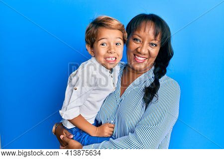Hispanic family of mother and son hugging together with love looking positive and happy standing and smiling with a confident smile showing teeth