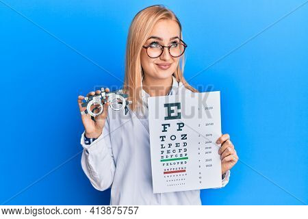 Beautiful caucasian optician woman holding optometry glasses and medical exam smiling looking to the side and staring away thinking.