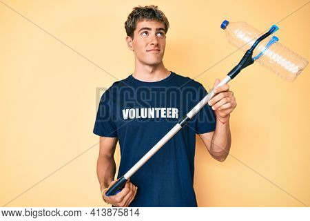 Young handsome man recycling plastic bottle holding litter pick up tool smiling looking to the side and staring away thinking.