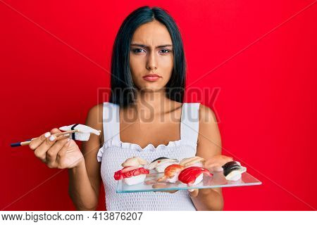 Young brunette woman eating butterfish sushi using chopsticks clueless and confused expression. doubt concept.