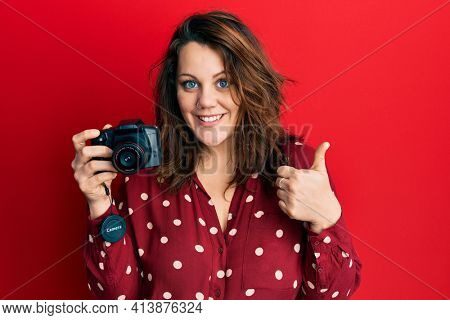 Young caucasian woman holding reflex camera smiling happy and positive, thumb up doing excellent and approval sign