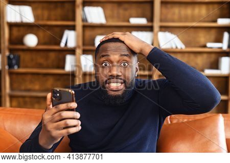 Discouraged African-american Man Grabbed His Head, Holding A Smartphone, Looks At The Camera With Ey