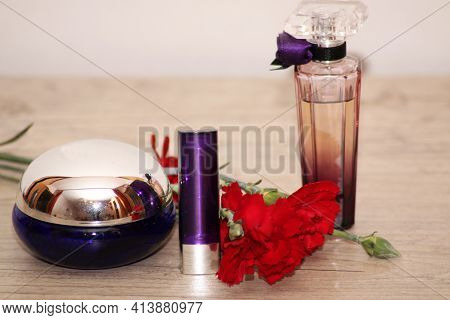 Perfume Set On A Wooden Table Is Decorated With A Bouquet Of Carnations. The Background Is White. A