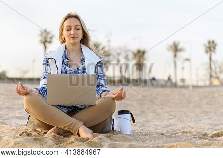 Casual Young Woman Meditating On The Empty Beach With Laptop And Coffee Cup. Freelance, Time Managem