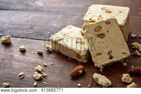 Halva Almond Nuts Slices On Wooden Table Background